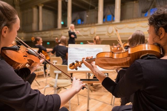 un orchestre symphonique en train de jouer vu depuis le pupitre des violons